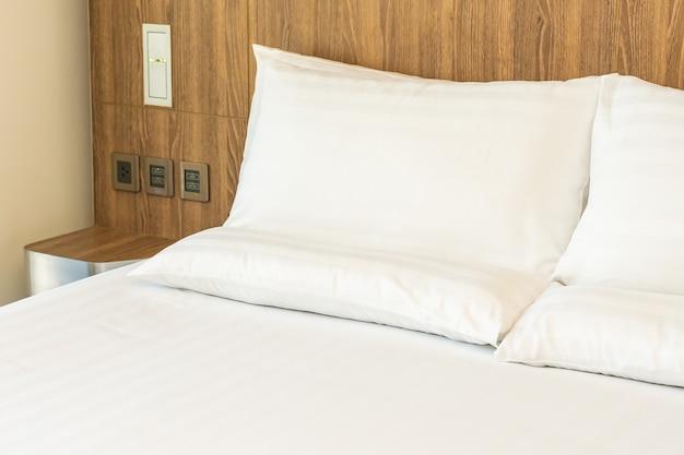 Almofadas brancas confortáveis na cama com cobertor