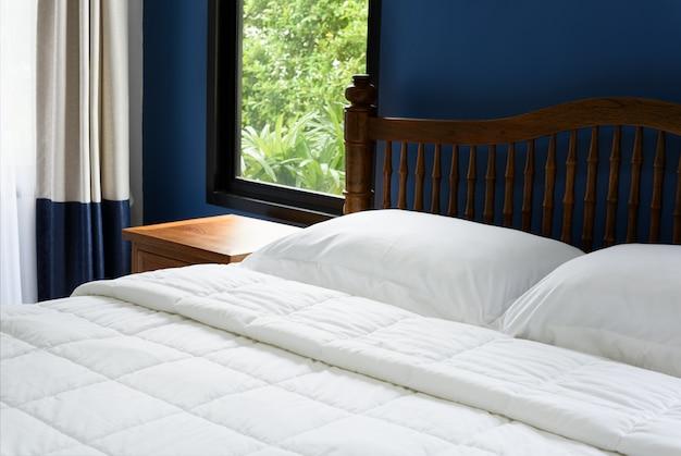 Almofadas brancas e lençóis da cama e mesa de cabeceira de madeira no interior azul do quarto em tempo de manhã