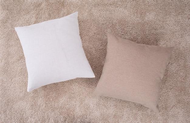 Almofadas brancas e marrons no tapete marrom. dois travesseiros com estojos de estopa.
