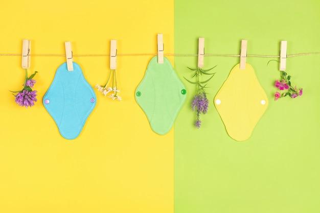 Almofadas coloridas eco reutilizáveis de tecido menstrual e flores silvestres no varal