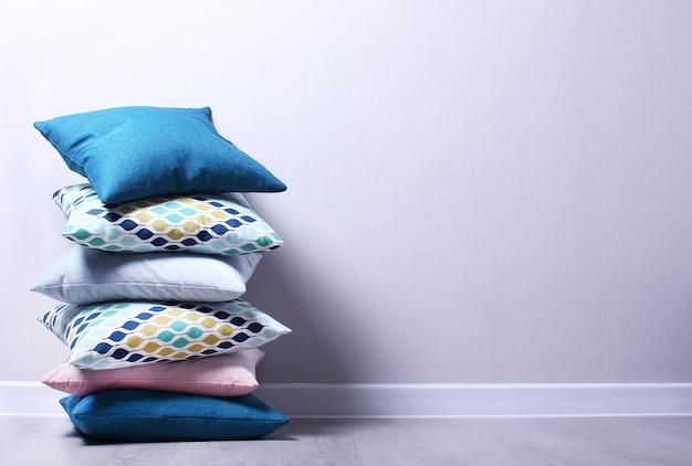 Almofadas coloridas elegantes no quarto na parede cinza. almofadas azuis, rosa e azuis escuras no chão. copie o espaço, conceito de casa aconchegante.