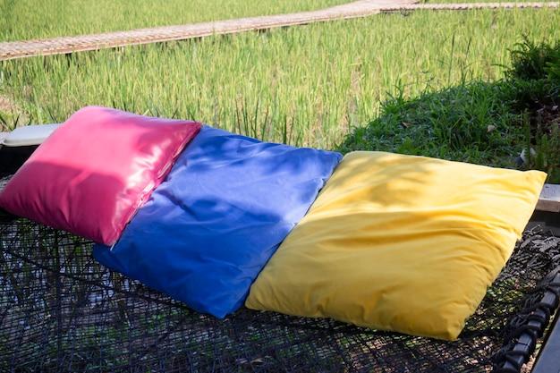 Almofadas coloridas no assento líquido entre a natureza