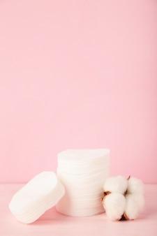 Almofadas cosméticas descartáveis higiênicas e flores de algodão em fundo rosa