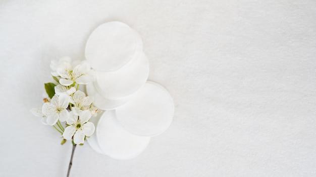 Almofadas cosméticas e flor do produto higiênico no fundo branco