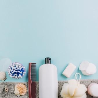 Almofadas de algodão e cotonetes perto de garrafa de cosméticos