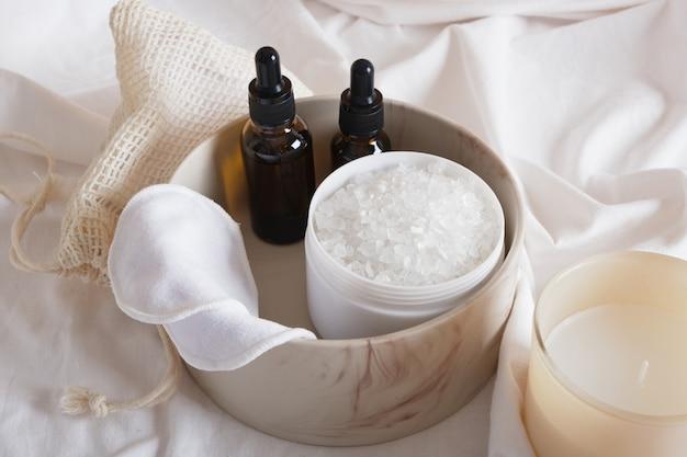 Almofadas de algodão reutilizáveis, óleo ou soro aromático, sal de banho e vela aromática em um lençol branco, conceito de spa ecológico