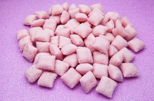 Almofadas de doce doce misturado em fundo rosa