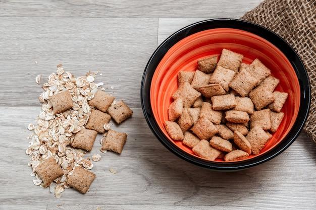 Almofadas de grãos de cinco cereais com recheio de chocolate sobre tela na mesa de madeira
