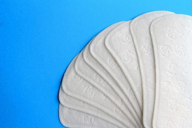 Almofadas de higiene feminina dispostas como um fã em um fundo azul