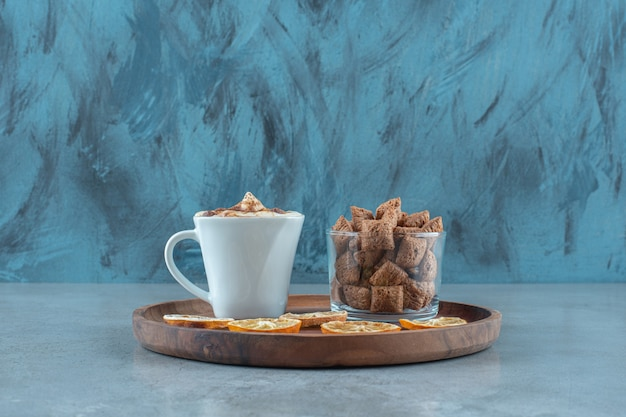 Almofadas de milho em um copo ao lado de rodelas de limão e uma xícara de cappuccino em uma placa de madeira, na mesa azul.