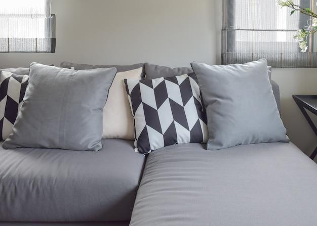 Almofadas de padrão de paralelogramo preto e branco no sofá confortável de l forma cinza