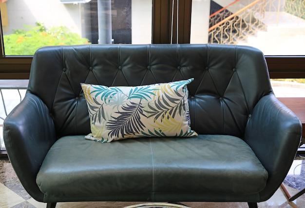 Almofadas de tecido no sofá de couro