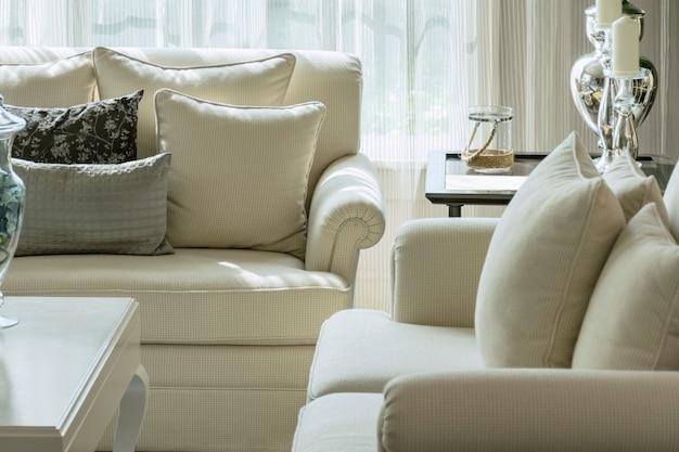 Almofadas decorativas brancas e cinzas em um sofá casual na sala de estar