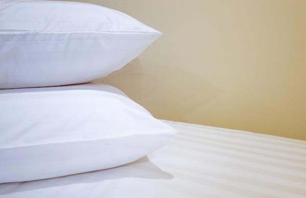 Almofadas duplas na cama que se preparando para o fundo do hóspede.