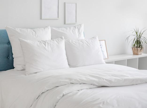 Almofadas e edredons brancos na cama azul.