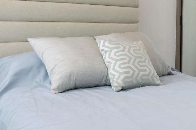 Almofadas macias confortáveis na cama azul clara