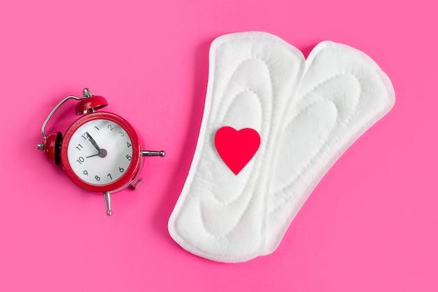 Almofadas menstruais, despertador em um fundo rosa.