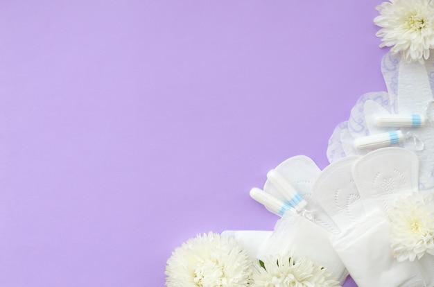 Almofadas menstruais e tampões com flores brancas macias sobre fundo lilás pastel