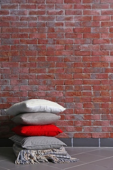 Almofadas multicoloridas em um fundo de parede de tijolos