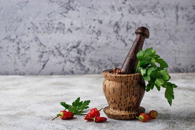 Almofariz de madeira com pimenta e salsa. foco seletivo