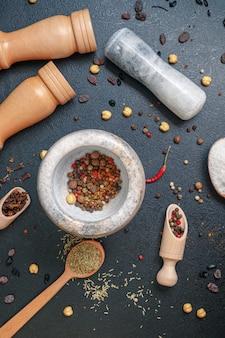 Almofariz de pedra com pimenta e colheres de pau com especiarias na mesa, vista superior