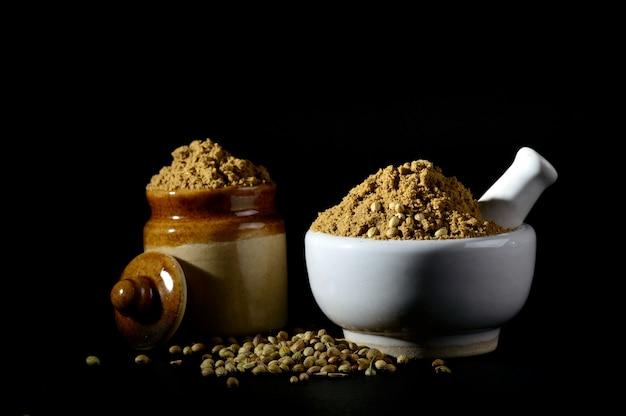 Almofariz e pilão com coentro em pó e sementes.