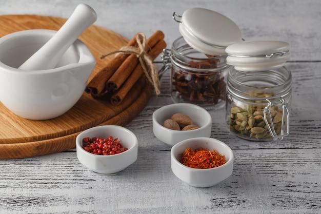 Almofariz e pilão com pimenta e especiarias na mesa de madeira