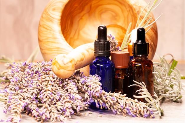Almofariz e pilão de lavanda e garrafas de óleos essenciais para aromaterapia