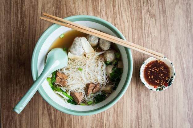 Almôndega de carne de porco de sopa de macarrão e tofu na tigela com pauzinho e molho