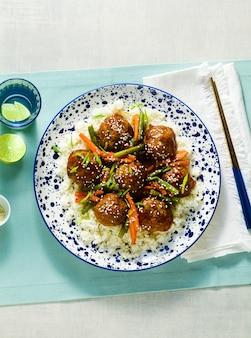 Almôndegas asiáticas veganas sem carne em molho agridoce com arroz e legumes cozidos. almoço balanceado ou jantar saudável. comida de rua
