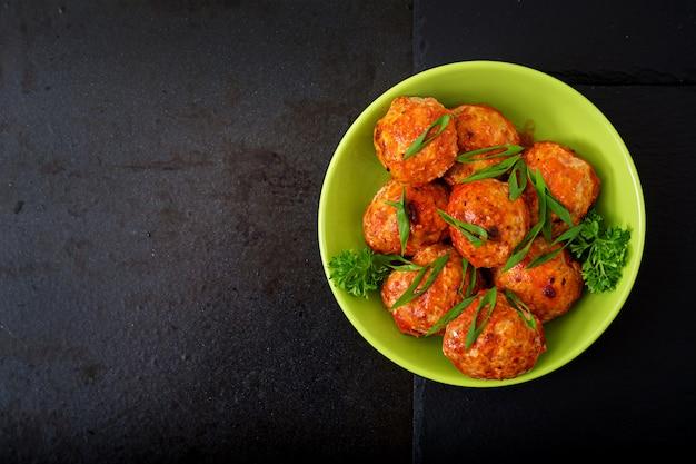 Almôndegas assadas de filé de frango em molho de tomate.