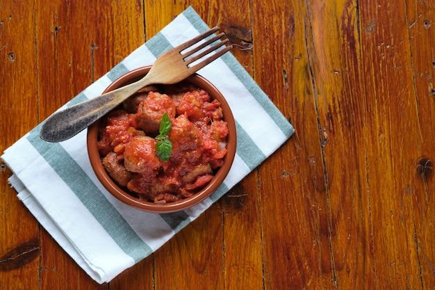 Almôndegas com molho de tomate em madeira rústica e vista de cima