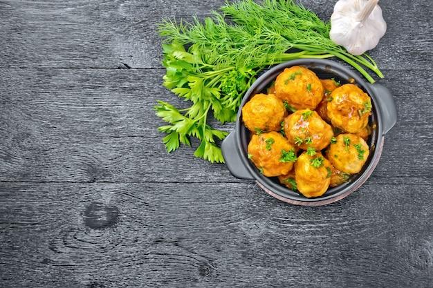 Almôndegas com molho de tomate em um braseiro com salsa, endro e alho em um fundo de tábua de madeira por cima