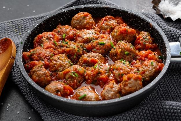 Almôndegas com molho de tomate servidas na frigideira em fundo escuro.