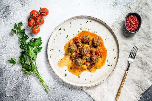 Almôndegas de carne com molho de tomate e legumes em uma panela. fundo cinza. vista do topo