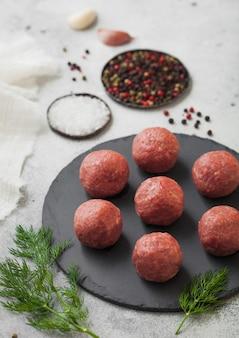 Almôndegas de carne crua fresca na placa de pedra redonda com pimenta, sal e alho na superfície clara com endro.