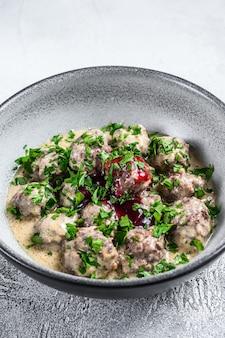 Almôndegas de carne moída com molho de natas em um prato.