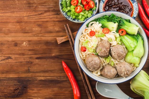 Almôndegas de comida chinesa servidas com macarrão,
