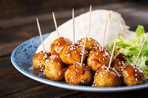 Almôndegas em esmalte agridoce em um prato com pão árabe e legumes em estilo marroquino em uma mesa de madeira.