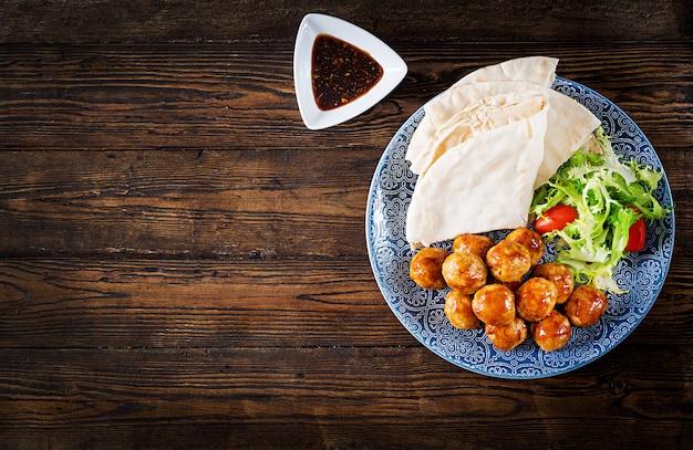 Almôndegas em esmalte doce e azedo em um prato com pão pita e legumes em um estilo marroquino