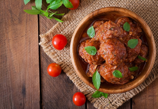 Almôndegas em molho de tomate agridoce e manjericão em uma tigela de madeira