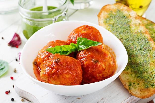 Almôndegas em molho de tomate e torradas com pesto de manjericão. jantar. comida saborosa.