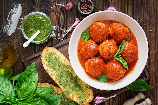 Almôndegas em molho de tomate e torradas com pesto de manjericão.