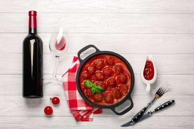Almôndegas em molho de tomate em uma frigideira com uma garrafa de vinho, dois copos, faca e garfo em uma placa de madeira branca