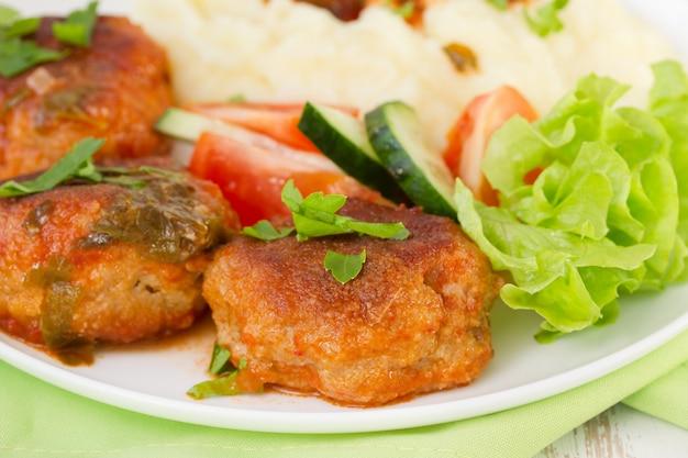 Almôndegas fritas com purê de batata, molho e salada