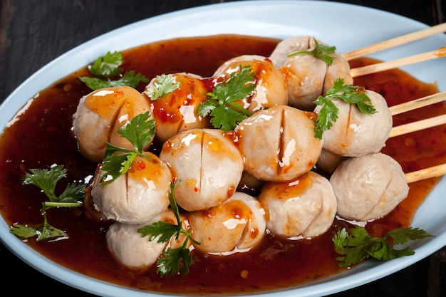 Almôndegas grelhadas espeto de bambu na placa branca com molho picante na mesa de madeira, bolas de carne grelhadas comida de rua da tailândia.