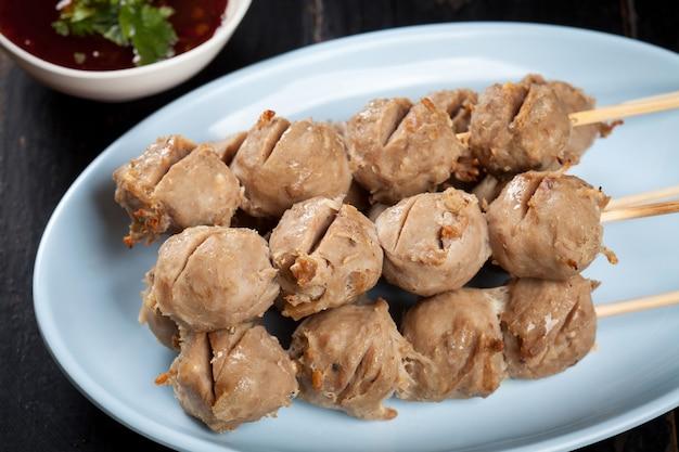 Almôndegas grelhadas espeto de bambu na placa branca com molho picante na mesa de madeira, bolinhas de carne grelhadas tendão comida de rua da tailândia.