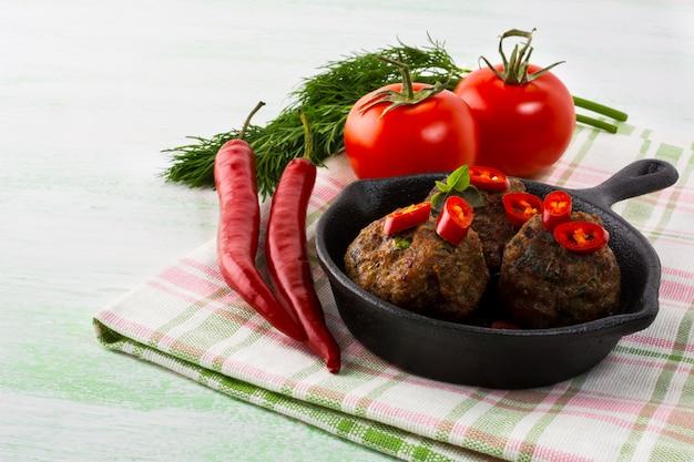 Almôndegas grelhadas, servidas com fatias de pimenta na frigideira de ferro fundido