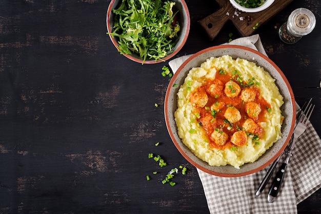 Almôndegas no molho de tomate com as batatas trituradas na bacia. vista do topo