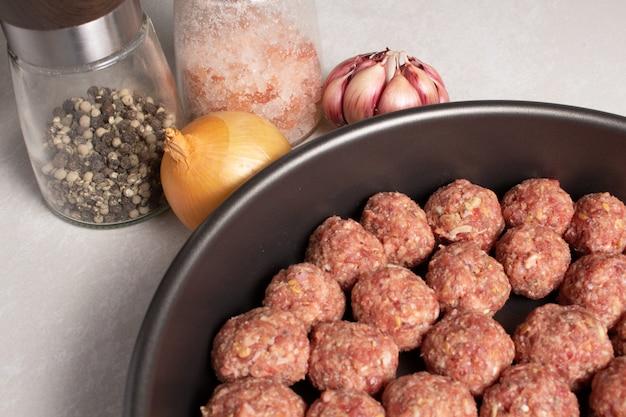 Almôndegas picadas cruas prontas para o conceito de culinária prepary em fundo claro